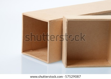 Cardboard box laying on it's side with separate lid with reflection - stock photo