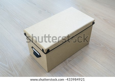 Cardboard box with a lid on the wooden background.