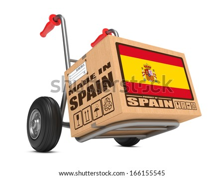 Cardboard Box with Flag of Spain and Made in Spain Slogan on Hand Truck White Background. Free Shipping Concept. - stock photo