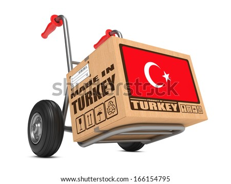 Cardboard Box with Flag of Turkey and Made in Turkey Slogan on Hand Truck White Background. Free Shipping Concept. - stock photo
