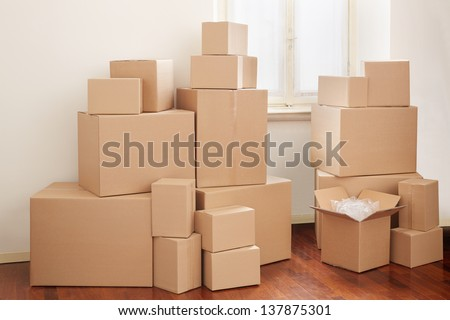 Cardboard boxes in apartment, moving day - stock photo