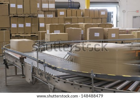 Cardboard boxes on conveyor belt in distribution warehouse - stock photo