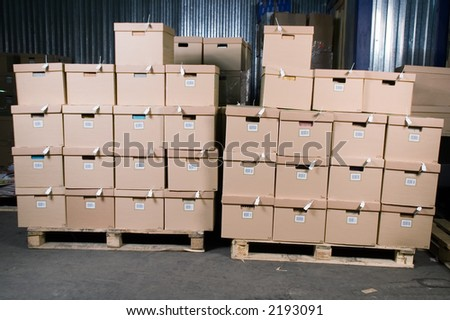Cardboard boxes on the shelves in the warehouse - stock photo