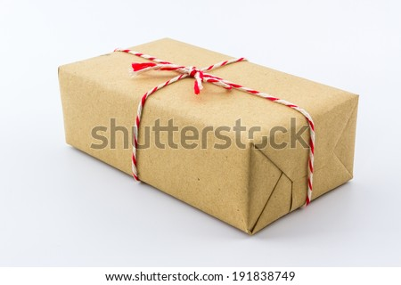 Cardboard carton wrapped with brown paper, tied with string.  - stock photo