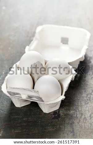 Cardboard egg box with eggs on wooden table - stock photo