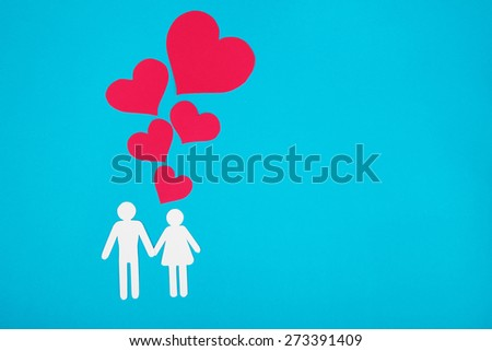 Cardboard figures of two people on a blue background. The symbol of unity and happiness. - stock photo