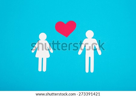Cardboard figures of two peoples on a blue background. The symbol of unity and happiness. - stock photo