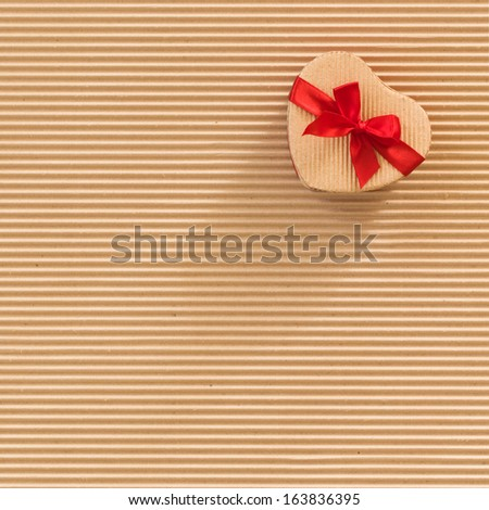 Cardboard gift box with red bow, heart shaped, on corrugated cardboard background, square format  - stock photo