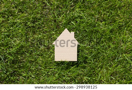 Cardboard house on green grass  - stock photo
