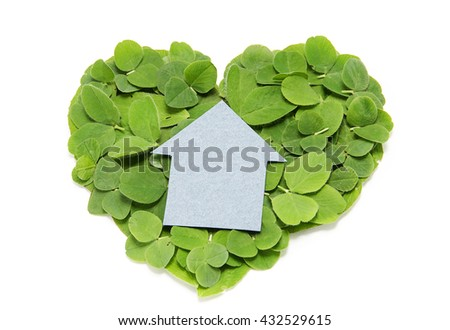 Cardboard house on the heart of a clover leaf. Eco-friendly housing
