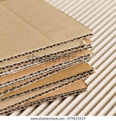 Cardboard pile on corrugated cardboard texture - stock photo