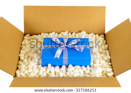 Cardboard shipping delivery box opened with blue gift surprise inside and polystyrene packing pieces. - stock photo
