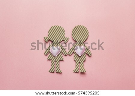 Cardboard silhouettes girl and boy with hearts on pink background. Valentine's Day background. Space for text. Top view.