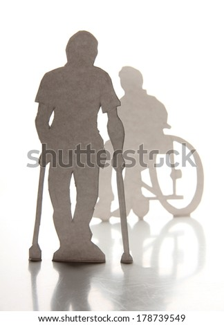 Cardboard silhouettes of people with crutches and a wheelchair - stock photo