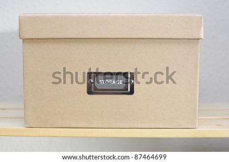 Cardboard storage box on shelf against plain wall. - stock photo