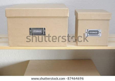 Cardboard storage boxes on shelf against plain wall. - stock photo