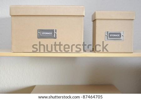 Cardboard storage boxes on shelf against plain wall. - stock photo