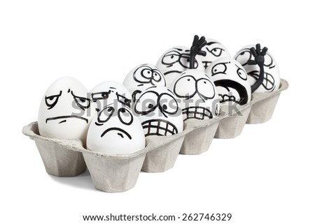 Cardboard tray with eggs which are drawn angry face isolated on white background - stock photo