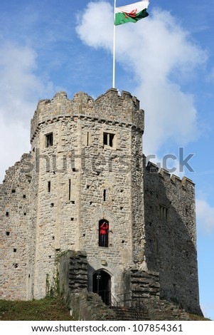 Cardiff castle on a sunny day, with the Welsh flag flying about it - stock photo