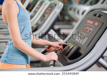 Cardio training. Rear view of young beautiful woman in sports clothing setting up her workout before running on a treadmill in the gym - stock photo