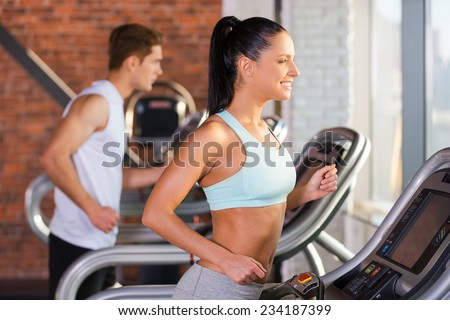 Cardio training. Side view of beautiful young woman running on a treadmill and smiling with man in the background - stock photo