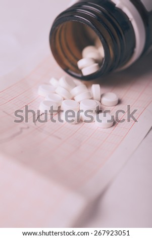 Cardiogram and nitroglycerin, the concept for strokes and  heart attacks - stock photo