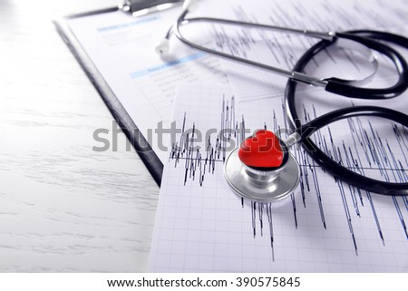 Cardiogram chart with medical stethoscope and small red heart on table closeup