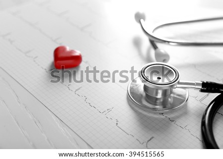 Cardiogram chart with medical stethoscope and small red heart on table closeup - stock photo