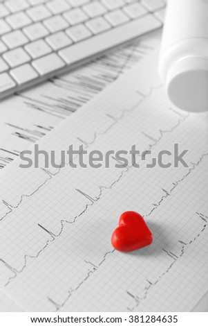 Cardiogram chart with small red heart and plastic bottle of medicines on table closeup - stock photo