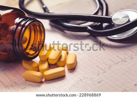 Cardiogram, stethoscope and yellow pills. Low contrast, toned photo. - stock photo