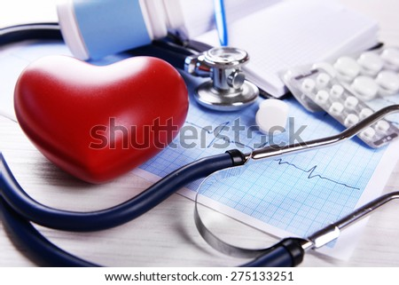 Cardiogram with stethoscope and red heart on table, closeup - stock photo