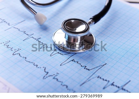 Cardiogram with stethoscope on table, closeup - stock photo
