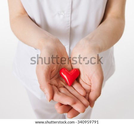 Cardiologist holding a ceramic red heart in palms, closeup shot - stock photo