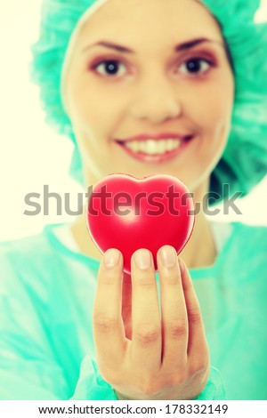 Cardiologist holding heart, isolated on white - focus on heart - stock photo