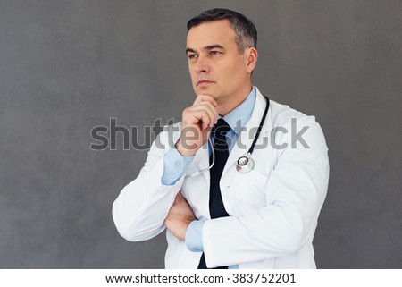 Cardiologist. Mature male doctor keeping hand on chin and looking away while standing against grey background - stock photo