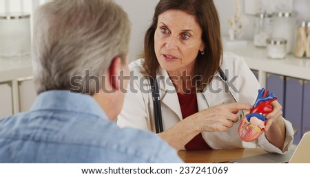 Cardiologist talking to elderly patient about his heart - stock photo