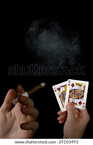Cards and cigar in the male hands with smoke on the black background