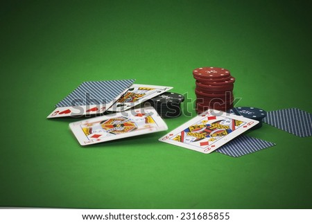 Cards and gambling chips over green background - stock photo