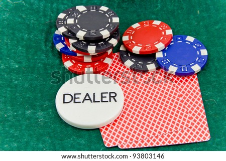 cards and stack of Poker chips and dealer button on a green background