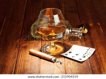 Cards, cigar and glass of whisky in spot light - stock photo