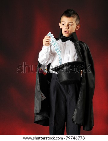 Cards flying from a hat into a young magician's hand. - stock photo