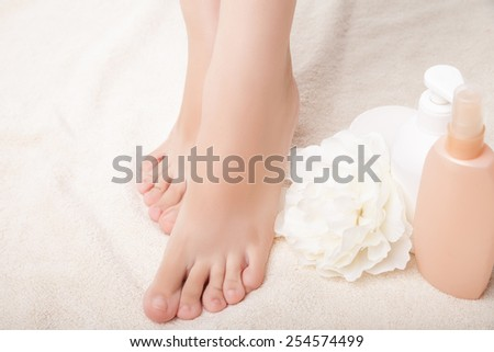 care for beautiful woman legs. Legs, flower and lotion bottle composition. Isolated over white background. - stock photo