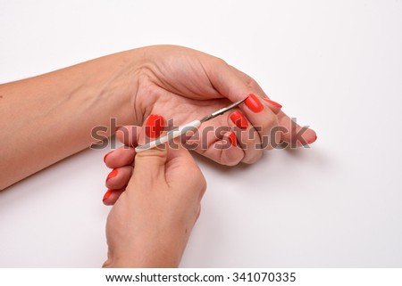 Care for cuticles. Hand holding scissors for manicure isolated on white background. Health and personal care
