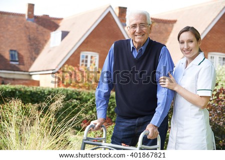 Care giver Helping Senior Man To Walk In Garden Using Walking Frame - stock photo