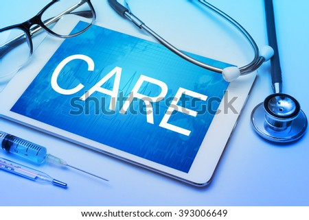 Care word on tablet screen with medical equipment on background - stock photo