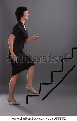 Career advancement concept. Business woman stepping up on stairs to gain her success with grey wall background. - stock photo