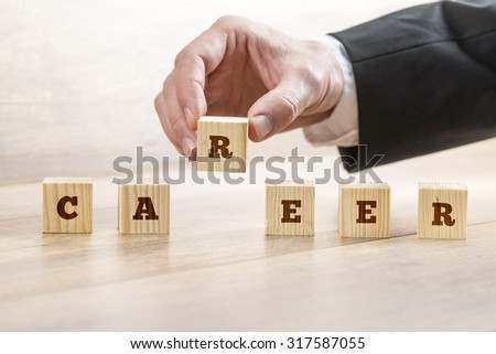 Career adviser assembling the word career with six wooden cubes  in a conceptual image of personal guidance towards self realization. - stock photo