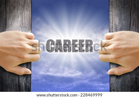 Career text in the blue sky behind hand opening a wooden door. - stock photo