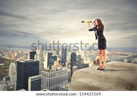 career woman looking with binoculars over the city - stock photo