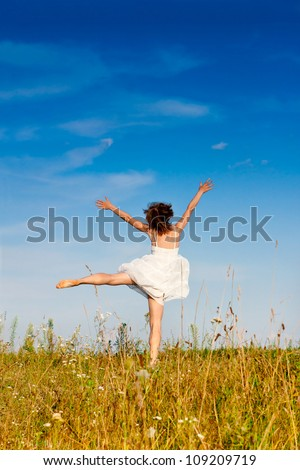 Carefree adorable girl with arms out in field. Summer. Freedom andjoy concept